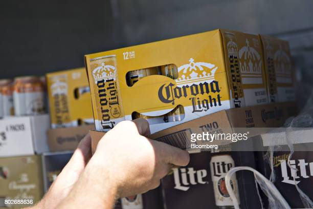 A worker unloads a case of Constellation Brands Inc Corona beer from truck during a delivery in Ottawa Illinois US on Tuesday June 27 2017...