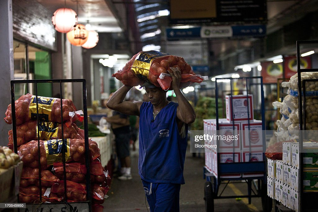 A worker unloads bags of onions at a market in Rio de Janeiro, Brazil, on Thursday, June 13, 2013. Brazilian retail sales rose in April at less than half the pace economists forecast as inflation erodes purchasing power, complicating the governments effort to boost growth. Photographer: Dado Galdieri/Bloomberg via Getty Images