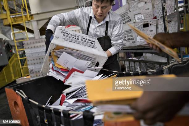 A worker unloads mail into a bin at the United States Postal Service Suburban processing and distribution center in Gaithersburg Maryland US on...