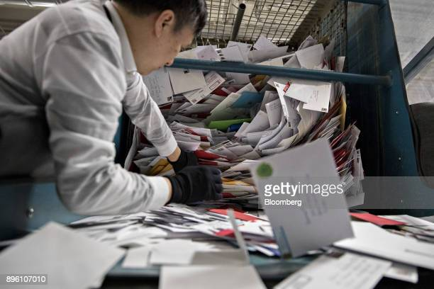 A worker unloads mail to a conveyor belt at the United States Postal Service Suburban processing and distribution center in Gaithersburg Maryland US...