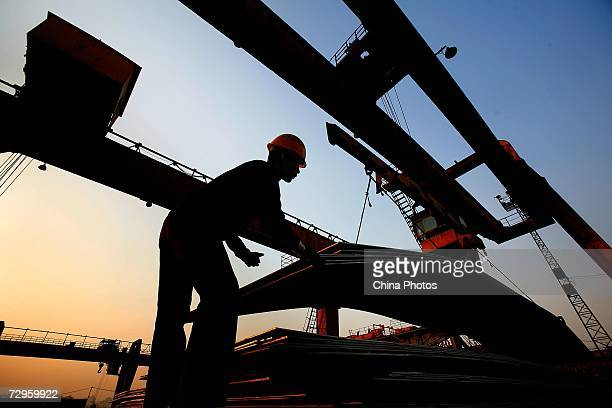 A worker unloads steel products from a crane at a factory of Shanghai Baosteel Group on January 9 2007 in Shanghai China Baosteel is China's largest...