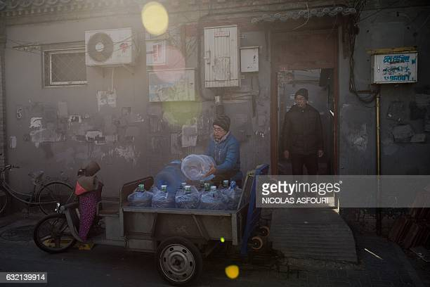 A worker unloads water bottles from his electric tricycle in Beijing on January 20 2017 China's economy grew last year at its slowest rate in more...