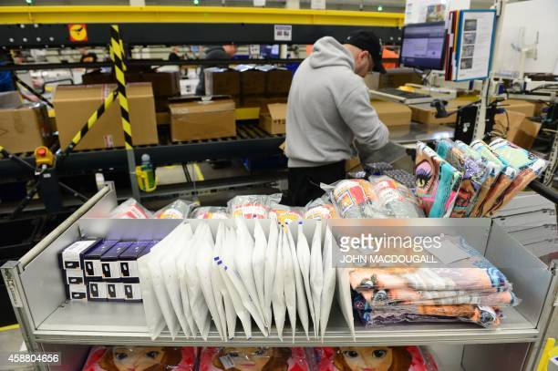 A worker unpacks incoming products at US online retail giant Amazon's Brieselang logistics center west of Berlin on November 11 2014 The center is...
