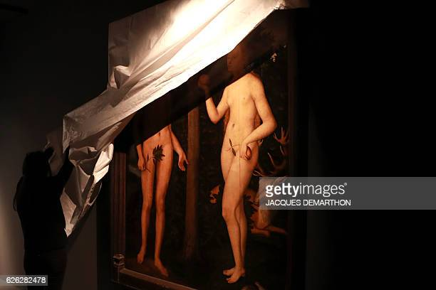 A worker unveils a copy of 'Adam and Eve' an oil by German Renaissance painter Lucas Cranach the Elder on November 28 2016 at the Musee des Arts...