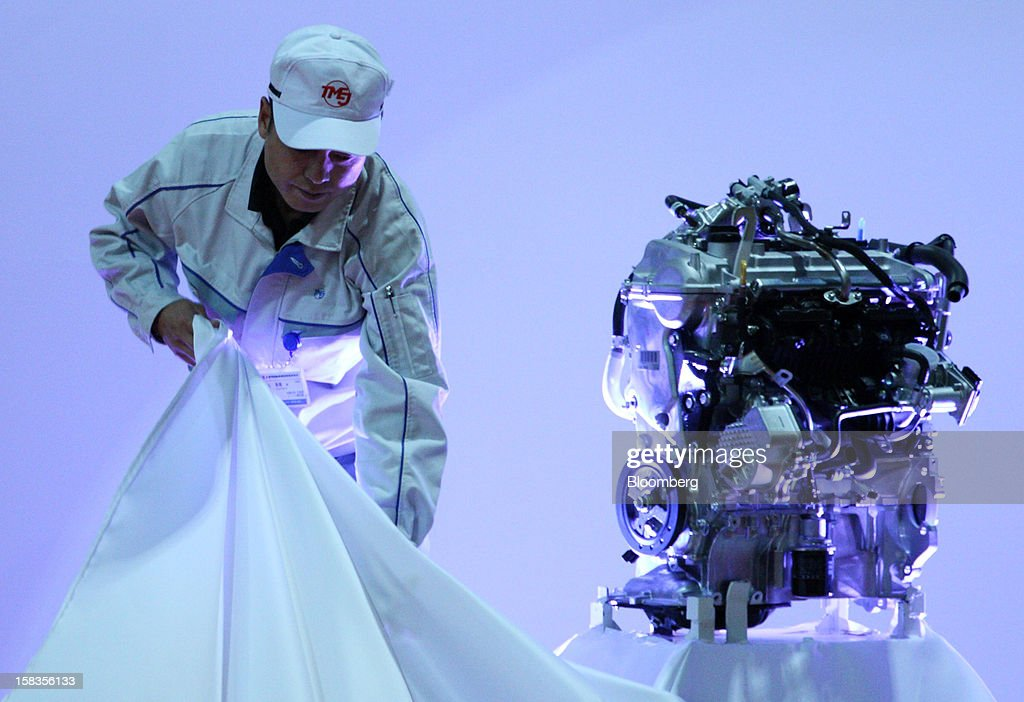 A worker unveils an engine for the Toyota Motor Corp. Aqua hybrid compact car during the line-off ceremony of Toyota Motor East Japan Inc.'s Miyagi Taiwa Plant in Taiwa, Miyagi Prefecture, Japan, on Friday, Dec. 14, 2012. Toyota Motor East Japan Inc. commenced operations at the plant today. Photographer: Tomohiro Ohsumi/Bloomberg via Getty Images