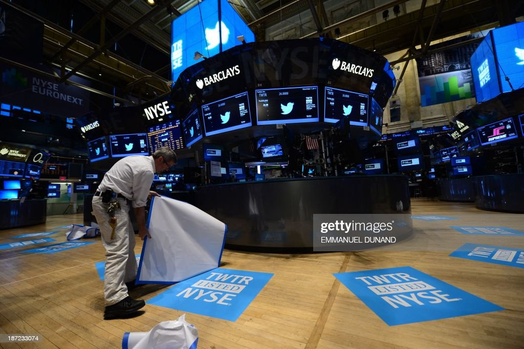 A worker unveils floor mats bearing the logo of Twitter and the symbol on which Twitter's stock will traded (TWTR) on the floor of the New York Stock Exchange (NYSE) on November 7, 2013 in New York. Twitter goes public on the NYSE today,and is expected to open at $26 per share, making the company worth an estimated 18 billion USD . AFP PHOTO/EMMANUEL DUNAND / AFP PHOTO / Emmanuel DUNAND