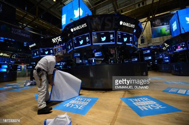 A worker unveils floor mats bearing the logo of Twitter and the symbol on which Twitter's stock will traded on the floor of the New York Stock...