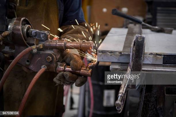 A worker use a spot welder on a metal door during production at the Metal Manufacturing Co facility in Sacramento California US on Thursday April 12...