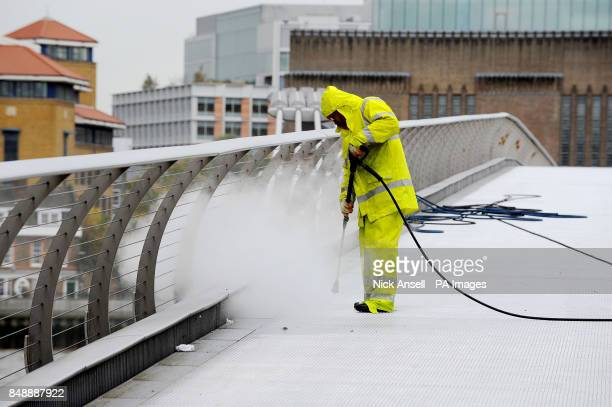 A worker uses a a high temperature pressure washer to remove chewing gum and clean the Millennium Bridge in London on the last day of it's annual...