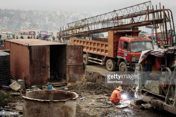 A worker uses a blow torch at a construction site for an underpass operated by Shanghai Construction Group Co in the Kalanki Chowk area of Kathmandu...