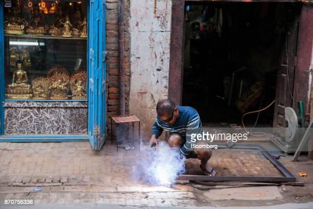 A worker uses a blow torch in Lalitpur Kathmandu Valley Nepal on Wednesday Nov 1 2017 India and China have often jostled for influence in Nepal a...
