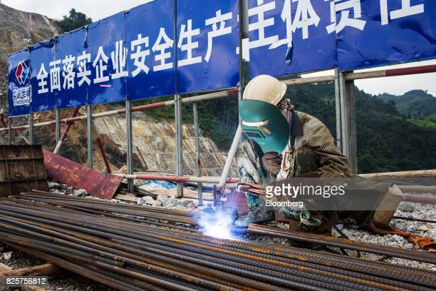 A worker uses a blowtorch at the Nam Tha 1 hydroelectric dam construction site being built by Power Construction Corp of China Ltd and to be operated...