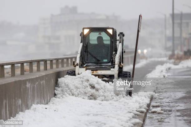 A worker uses a bobcat to clear snow from a sidewalk alongside Nantasket Beach during a winter storm that brought snow sleet and rain to the area on...