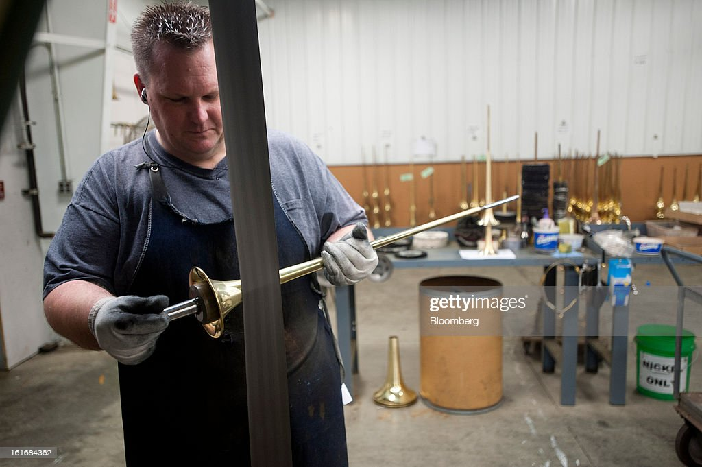 A worker uses a buffing wheel to remove any imperfections on a trumpet bell in the manufacturing department of the E.K Blessing Co. in Elkhart, Indiana, U.S., on Thursday, Feb. 7, 2013. Photographer: Ty Wright/Bloomberg via Getty Images