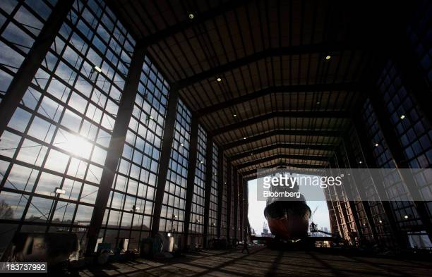 A worker uses a cherry picker to access the Pacer tugboat as it undergoes repairs at the Seaspan Vancouver Shipyard in North Vancouver British...