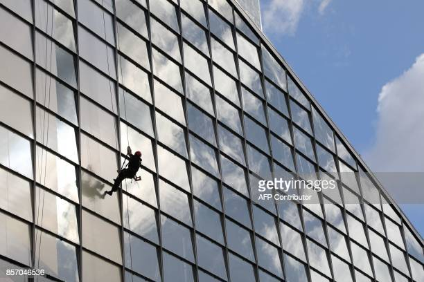 A worker uses a climbing rigging sytems to apply window size portions of an advertizing banner on the CNIT building in the La Defense business...