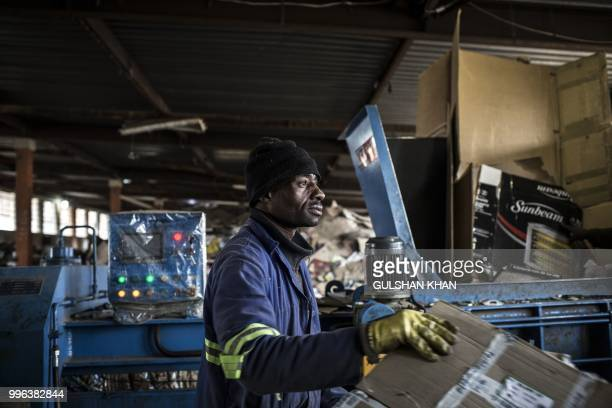 A worker uses a compression machine to flatten cardboards at the Mudimu Recycling a buy back centre in Selby Johannesburg where reclaimers bring...