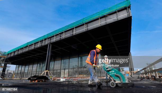 A worker uses a concrete floor grinder outside the main structure of the Neue Nationalgalerie Berlin's museum dedicated to 20th Century art as the...