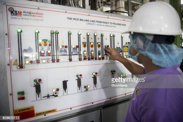 A worker uses a control panel for the rice milling line at the Amru Rice Co processing factory in Battambang Cambodia on Wednesday Aug 9 2017 Global...