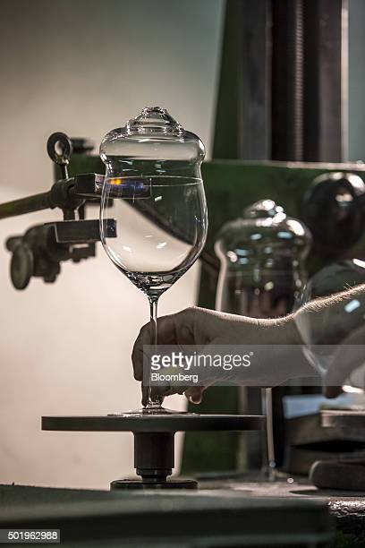 A worker uses a cutter to score the edge of a wine glass before removing the pipecap during the cracking process at the Novosad Son Glassworks in...