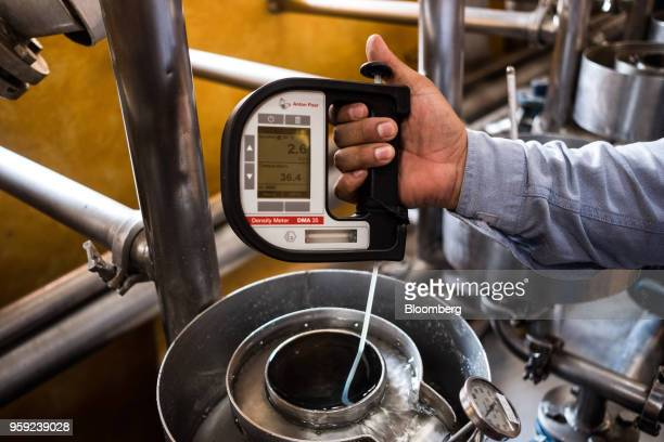 A worker uses a density meter to test alcohol content in tequila at the Becle SAB Jose Cuervo distillery in the town of Tequila Jalisco state Mexico...