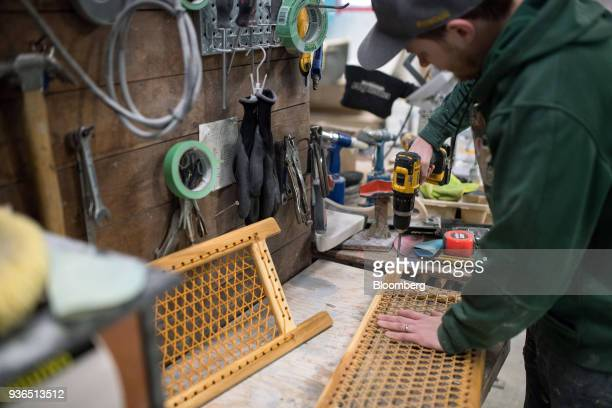 A worker uses a drill while making a seat for a canoe at the Holy Cow Canoe Co production facility in Guelph Ontario Canada on Thursday March 1 2018...