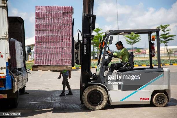 A worker uses a forklift to load cans of CocaCola Co brand Coke carbonated soft drink onto a truck at the CocaCola Cambodia Bottling Plant operated...