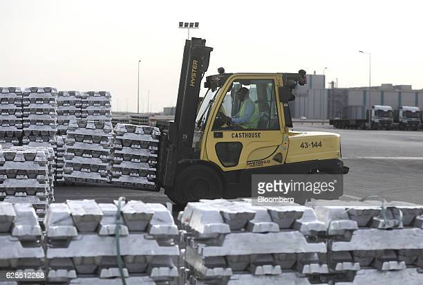 A worker uses a forklift truck to move pallets of aluminium ingots from the aluminium processing area at the Ras Al Khair Industrial City operated by...
