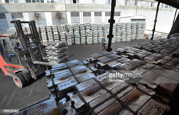 A worker uses a forklift truck to stack bundles of newly moulded aluminum ingots bearing the company logo of United Co Rusal Plc in a storage area at...
