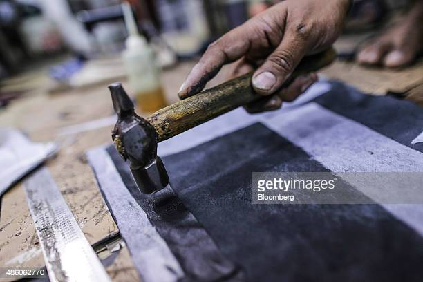 A worker uses a hammer on a piece of leather for a jacket at a leather workshop in the Dharavi slum area of Mumbai India on Saturday Aug 29 2015...