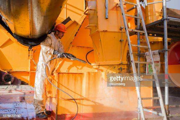 Worker uses a high pressure hose to clean metalwork during repair work on dredging vessel 'Daniel Leval' in a dry dock at the Port of Rouen in Rouen,...