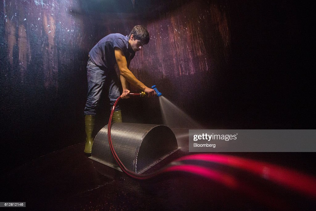 A worker uses a high pressure water hose to spray clean a fermentation tank during pinot noir wine manufacture on the Weingut Friedrich Becker Estate vineyard in Schweigen, Germany, on Tuesday, Oct. 4, 2016. Global warming has been good to German viticulture, with average temperatures up 1.4 degrees centigrade over the past 40 years, creating the perfect climate for notoriously finicky pinot noir vines. Photographer: Krisztian Bocsi/Bloomberg via Getty Images