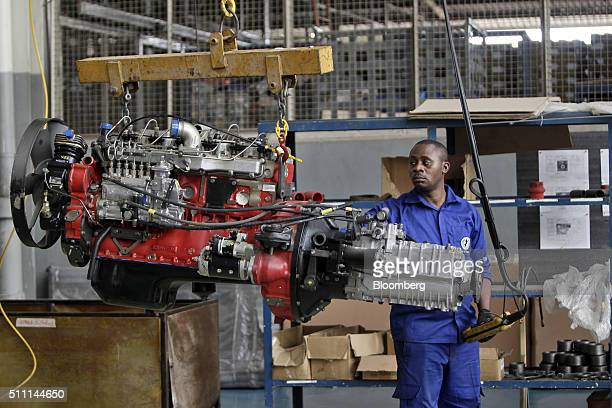 A worker uses a hoist to position the engine for a Stallion Civicbus at the Stallion Group vehicle assembly plant in Lagos Nigeria on Wednesday Feb...