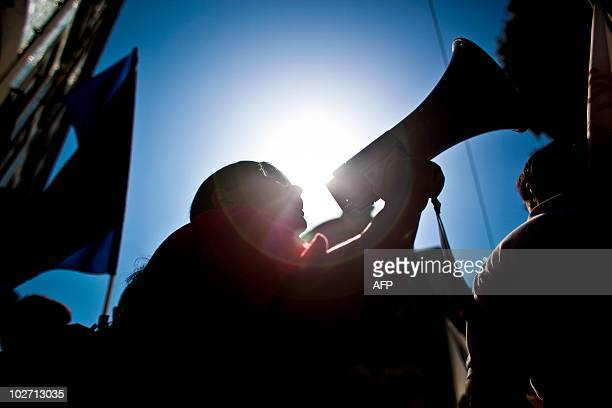 A worker uses a loudspeaker as he protests with thousands counterparts against government austerity measures during demonstrations launched by...