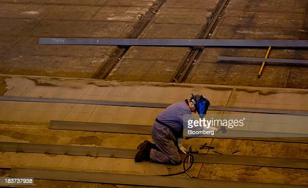 A worker uses a mallet while welding a portion of a barge under construction at the Seaspan Vancouver Shipyard in North Vancouver British Columbia...