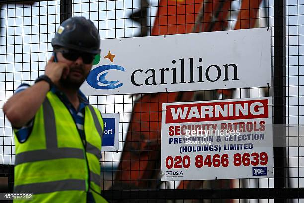 A worker uses a mobile phone outside the gates of a construction site for new apartment blocks built by Carillion Plc in the Canning Town district of...