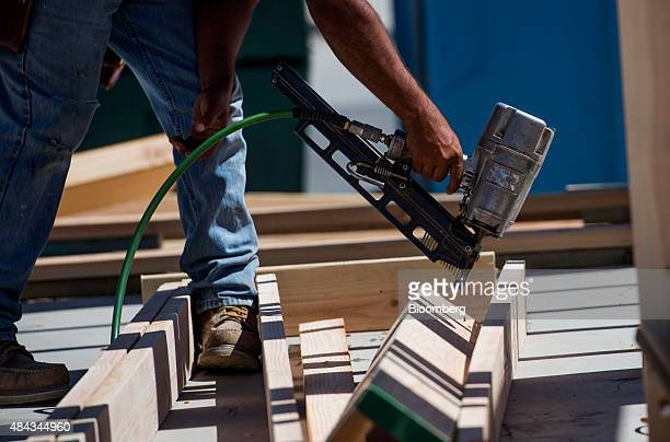 A worker uses a nail gun to build a frame for the wall of a house under construction at the KB Home Vineyard Crossing Community in Livermore...