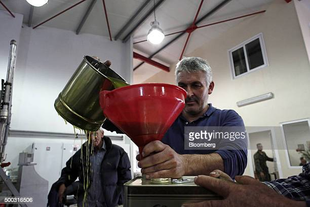 Worker uses a plastic funnel to fill a metal can with extra virgin olive oil at an olive oil processing plant in the Kalamata district village of...