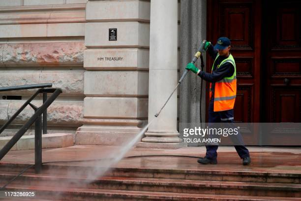 A worker uses a power hose to clean off the steps of the Treasury building in central London on October 3 2019 after protesters from climate group...