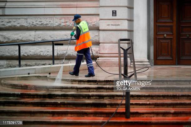 A worker uses a power hose to clean outside the Treasury building in central London on October 3 2019 after protesters from climate group Extinction...