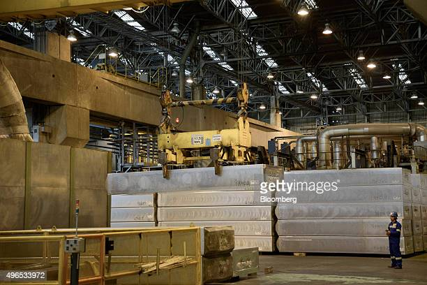 A worker uses a remote control to operate a crane moving an aluminum ingot made from recycled material at the Novelis Inc facility in Pindamonhangaba...