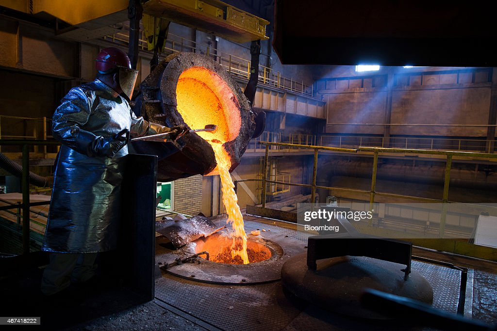 A worker uses a rod to control the flow of molten silver from a ladle before being cast at the KHGM Polska Miedz SA smelting plant in Glogow, Poland, on Monday, March 23, 2015. KGHM is the world's third-largest silver producer behind Fresnillo Plc and BHP Billiton Ltd. Photographer: Bartek Sadowski/Bloomberg via Getty Images
