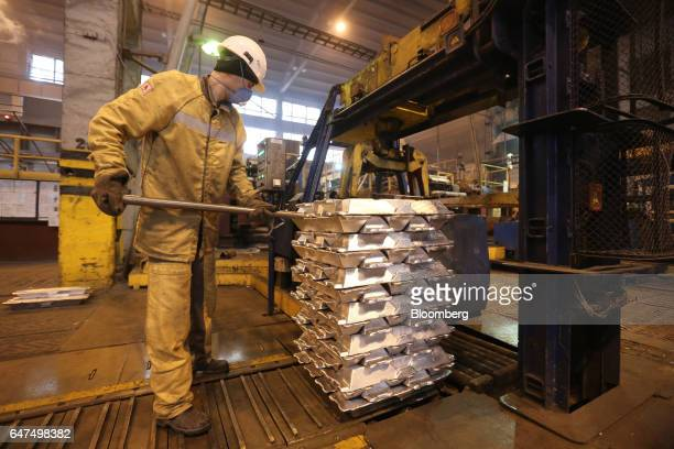 A worker uses a rod to position a pile of aluminum ingots before binding for shipping in the foundry at the Krasnoyarsk aluminum smelter operated by...
