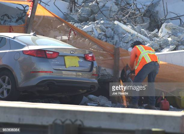 A worker uses a saw as law enforcement and members of the National Transportation Safety Board investigate the scene where a pedestrian bridge...