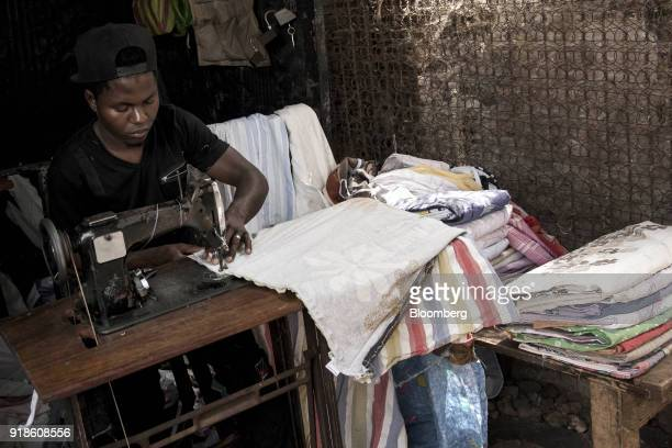 A worker uses a sewing machine to stitch fabric near Bandim market in Bissau GuineaBissau on Tuesday Feb 13 2018 The International Monetary Fund said...