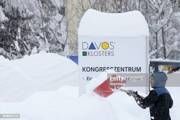 A worker uses a shovel to clear snow from the street after heavy snowfall ahead of the World Economic Forum in Davos Switzerland on Monday Jan 22...
