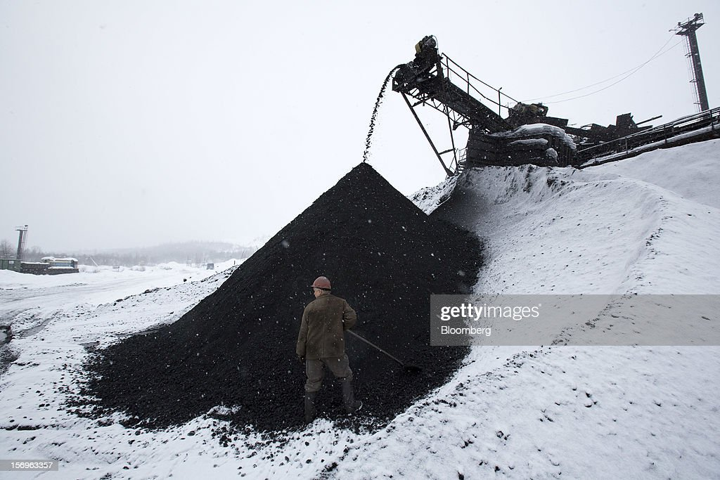 A worker uses a shovel to take a coal sample from a storage mound at the Sibirginsky open pit coal mine, owned by OAO Mechel and operated by Southern Kuzbass Coal Co., near Myski, in Kemerovo region of Siberia, Russia, on Friday, Nov. 23, 2012. OAO Mechel is Russia's biggest maker of steelmaking coal. Photographer: Andrey Rudakov/Bloomberg via Getty Images