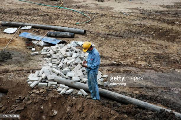 A worker uses a smartphone on a construction site for an underpass operated by Shanghai Construction Group Co in the Kalanki Chowk district of...