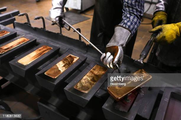 A worker uses a special tool to remove red hot gold ingots from their molds in the foundry at the JSC Krastsvetmet nonferrous metals plant in...