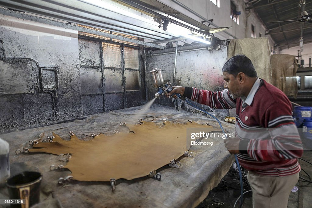 A worker uses a spray gun to treat a sheet of leather at the Jalandhar Leather Pvt tannery in Jalandhar Punjab India on Saturday Jan 21 2017 India`s..